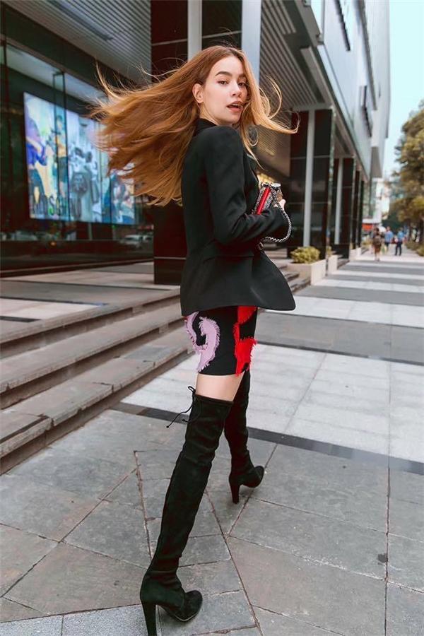 Với boots cổ cao, nữ ca sĩ kết hợp váy ngắn suông hoặc bó sát, kèmáo vestbên ngoài.
