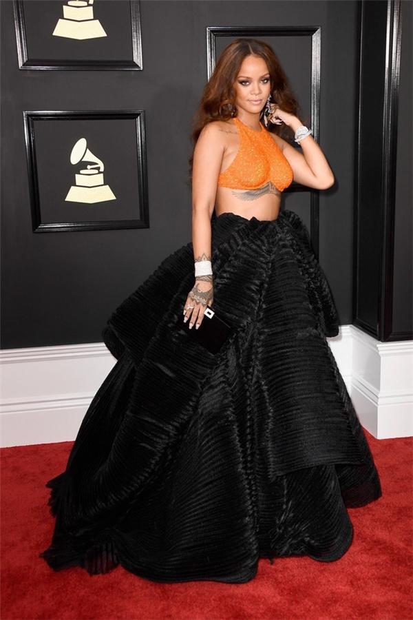 """Trang phục Rihanna được nhận xét có phần """"hiền"""" hơn những bộ cánh trước đó tại Grammy. Nữ ca sĩ kết hợp áo crap top màu xam nổi bật kết hợp chân váy phồng xòe."""