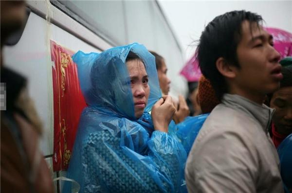 Mẹ lặng lẽ đội áo mưa tiễn con đitrong nỗi xúc động ngậptràn.