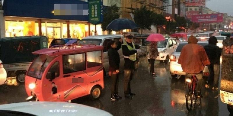 Ấm lòng người phụ nữ che dù cho viên cảnh sát dưới trời mưa