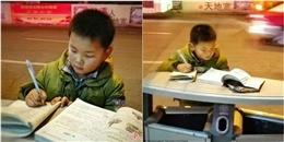 Cậu bé kê vở trên nắp thùng rác học bài cạnh xe khoai nướng của mẹ