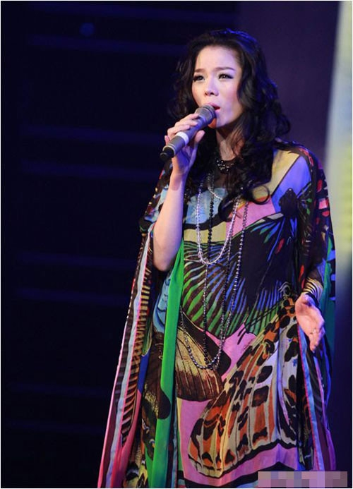 Tuy nhiên, chị đã khéo léo chọn cho mình chiếc đầm suông với nhiều họa tiết sặc sỡ để che đi phần nào bụng bầu và tự tin thể hiện các ca khúc trên sân khấu.