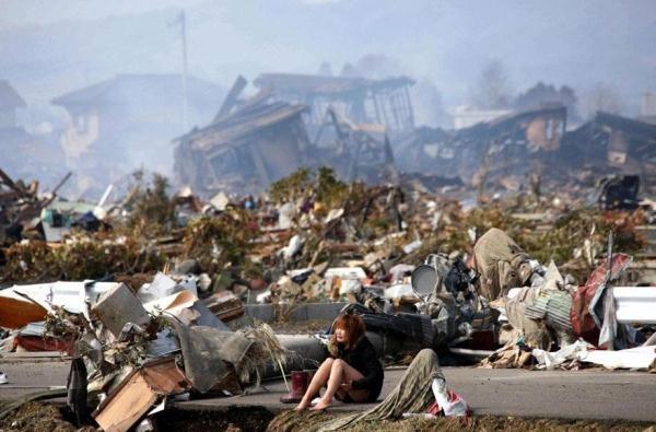 Một phụ nữ ngồi bệch xuống đất giữa đống đổ nát sau một trận động đất lớn và cơn sóng thần ở khu vực Natori, miền Bắc Nhật Bản vào tháng 3 năm 2011.