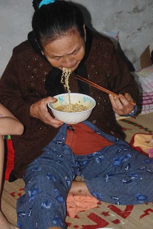 """""""Bão mà chú. May mà còn có mỳ tôm để ăn"""", cụ Nguyễn Thị Như (67 tuổi, đang trú ẩn tại nhà A7, P Nại Hiên Đông) vừa bê tô mì tôm vừa nói với phóng viên"""