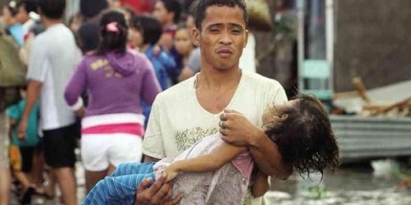 Một người đàn ông bế trên tay con gái bé nhỏ xấu số của mình sau khi siêu bão hủy diệt thành phố Tacloban. Ảnh: Inquirer.
