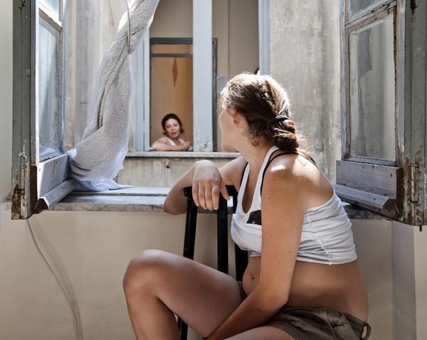 Carla nói chuyện với hàng xóm qua cửa sổ