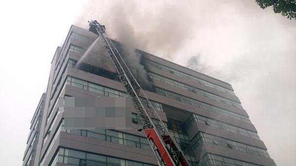 Xe thang chuyên dụng vươn lên tầng 9, để vòi rồng phun nước dập lửa ở điểm cháy gốc