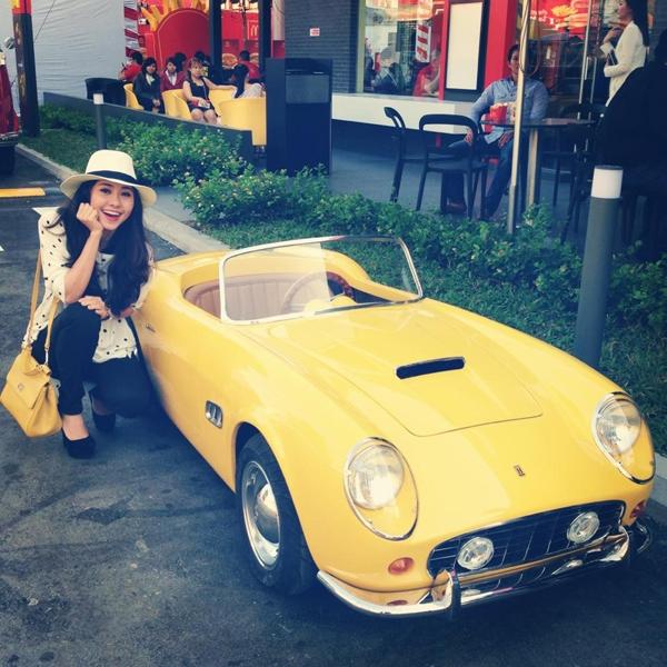 """...thì Tường Vi tạo dáng xì tin bên """"siêu xe mini"""" màu vàng, nữ diễn viên tỏ ra khá phấn khích muốn...ngồi vào xe chạy thử mà không vừa."""
