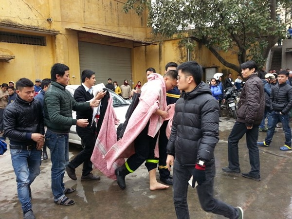 Một chiến sỹ cảnh sát PCCC bị bén lửa phía lưng phải dùng chăn để khống chế - Ảnh: Tiền Phong