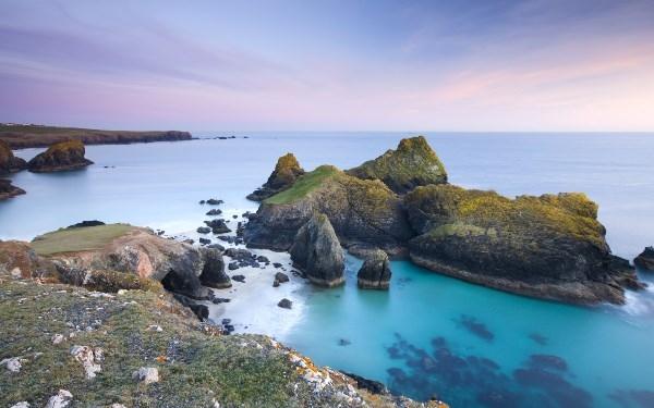 Vùng biển Kynace Cove nổi bật với những phiến đá lớn như được nhuộm màu lạ mắt, còn dưới chân là dòng nước trong xanh hiền hòa bên cát trắng.