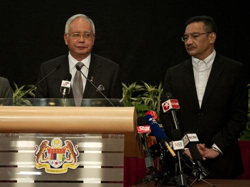 Thủ tướng Malaysia (trái) phát biểu tại Trung tâm Thương mại Thế giới Putra ở thủ đô Kuala Lumpur, Malaysia tối 24/3. Người đứng cạnh ông là Bộ trưởng Quốc phòng kiêm quyền Bộ trưởng Giao thông Hishammuddin Hussein. Ảnh: AFP.