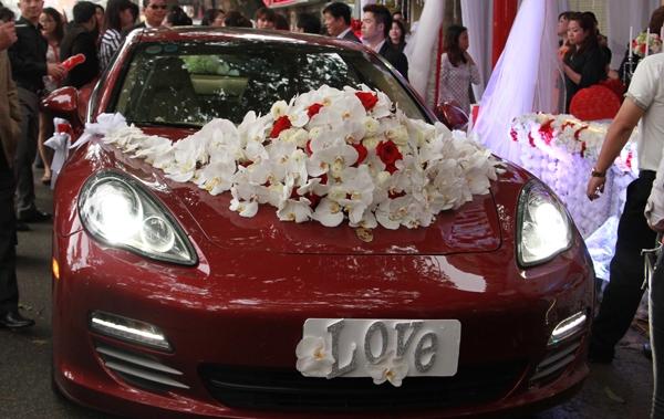 Tuấn Hưng dùng xe Porsche đỏ đi đón dâu. Anh dùng hoa lan hồ điệp trắng trang trí xe, điểm xuyết là hoa hồng đỏ thắm. Đây cũng chính là xe hơi của cô dâu Hương Baby đang sở hữu - Tin sao Viet - Tin tuc sao Viet - Scandal sao Viet - Tin tuc cua Sao - Tin cua Sao