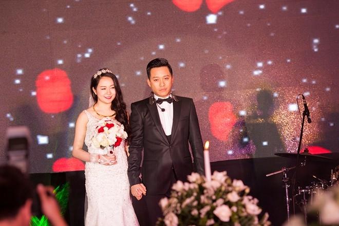 Cô dâu chú rể tay trong tay tiến lên sân khấu.