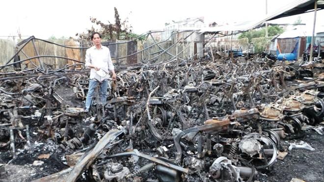 Anh Nhân đứng giữa hàng trăm xe tay ga bị cháy rụi trong vụ hỏa hoạn.