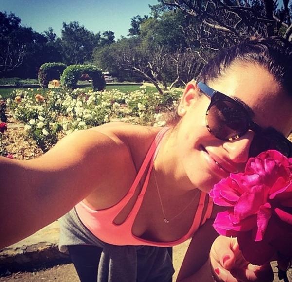 Lea Michele đang tận hưởng mùi thơm từ những cánh hoa trong một chuyến đi dạo,