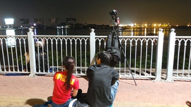 Hai bạn trẻ chọn được cho mình chỗ ngồi lý tưởng và chuẩn bị sẵn máy ảnh ghi lại thời điểm pháo hoa khai hỏa.