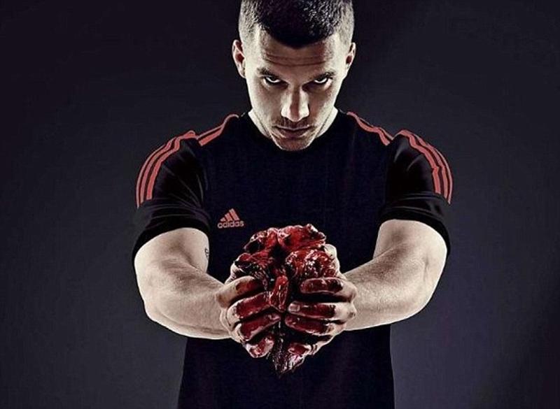 Podolski cầm quả tim của một con bò đangvấy máu