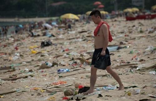 Người đàn ông nhăn mặt đi giữa đống rác. Ảnh: Barcroft.