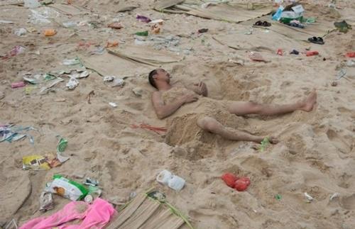 Một người đàn ông chợp mắt dưới cát, bên đống rác. Dù chính quyền đang nỗ lực dọn dẹp, phải mất một thời gian khung cảnh mới có thể trở lại như trước lễ hội. Ảnh: Barcroft