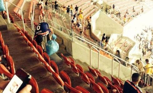 Một cổ động viên Nhật Bản đang nhặt rác ở khán đài. Ảnh: Yahoo Brazil.