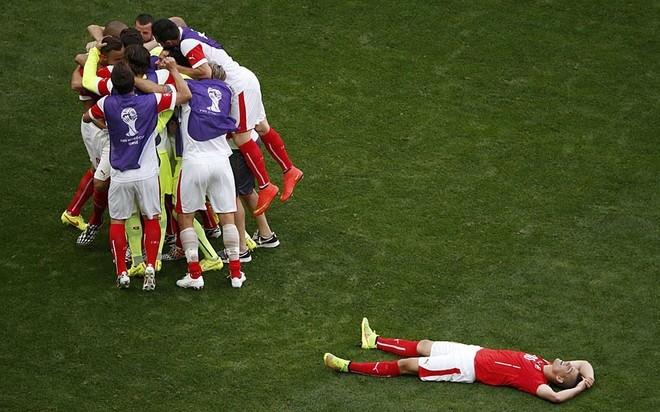 Đám đông cầu thủ Thụy Sĩ ôm lấy nhau vui sướng trong khi một cầu thủ Ecuador nằm thượt vì thất vọng. Trước đó, Thụy Sĩ lội ngược dòng thành công sau khi bị dẫn trước để giành chiến thắng 2-1. Bàn quyết định được ghi trong khoảng thời gian đá bù.