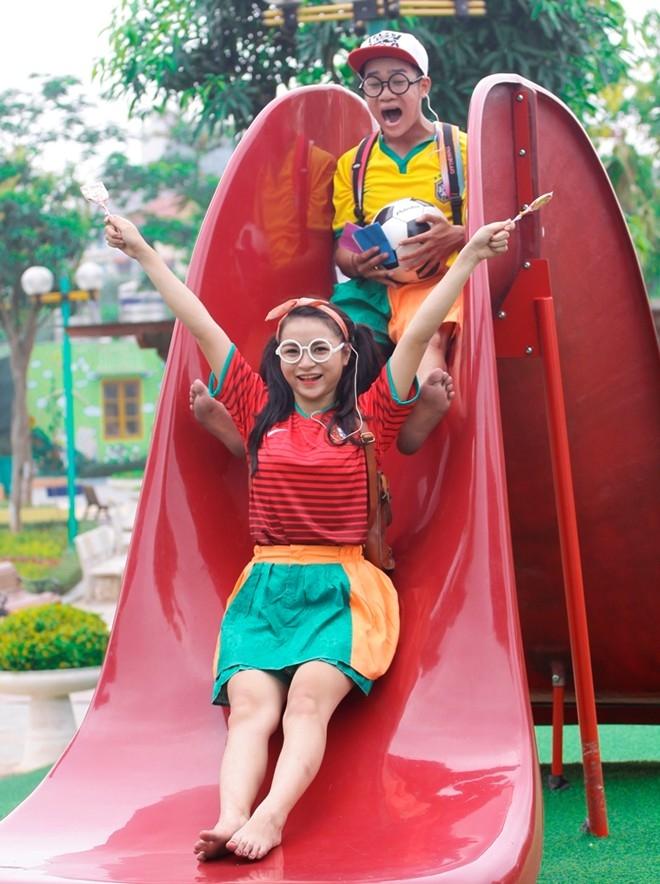 Cặp đôi tạo dáng nhí nhảnh trong sân chơi trẻ em.
