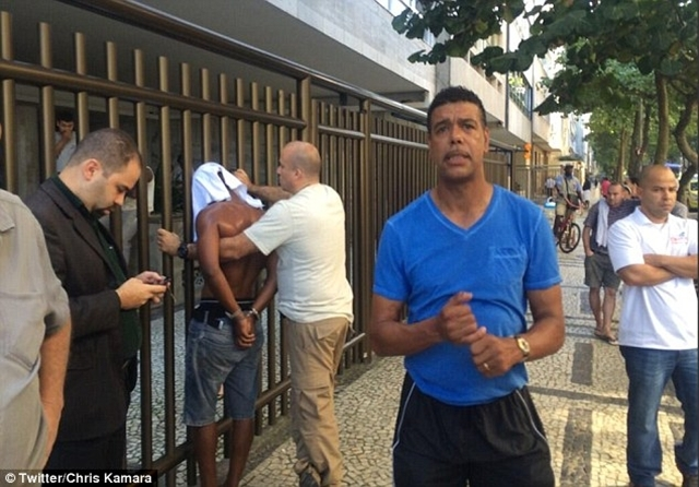 BLV Chris Kamara (áo xanh) và tên cướp bị cảnh sát còng tay ở phía sau
