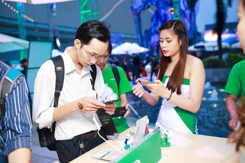 Một phóng viên ảnh háo hức trải nghiệm màn hình 2K đầu tiên tại Việt Nam và tính năng chụp ảnh siêu phân giải 50MP của Find 7 tại bàn trải nghiệm.