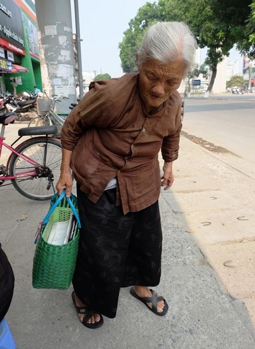 Mỗi sáng, bà lão lại còm cõi xách túi hàng đi bán.