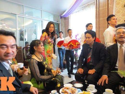 Nhà trai đưa sính lễ vào phòng khách nhà Trang Nhung. Bố của chú rể Hoàng Duy ngồi bên phải, cà vạt sọc chéo có gam đỏ ở giữa.