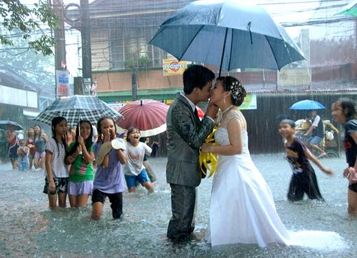 Nụ hôn hạnh phúc của một cô dâu và chú rễ trong cơn mưa của trận bão lụt ở Manila