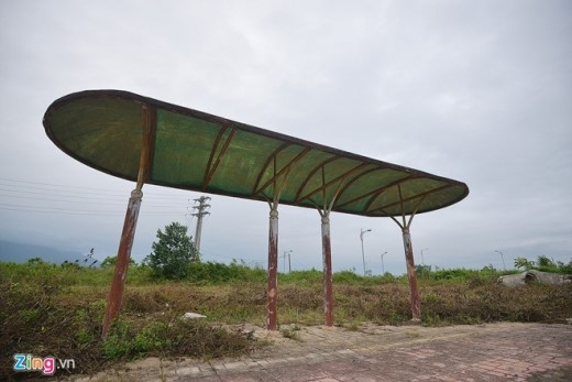 Phía ngoài cổng chính, hàng loạt trạm xe buýt được xây dựng để đón khách tham quan nhưng không hoạt động, các cột sắt hoen gỉ, cỏ dại mọc xung quanh.