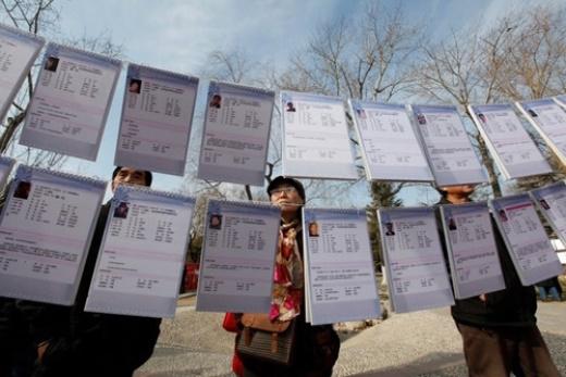 Các bậc phụ huynh lo lắng nhìn vào bản lý lịch của các ứng viên tại một sự kiện mai mối ở Bắc Kinh. Ảnh: Reuters.