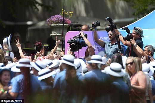 Những học sinh nữ trong bộ đồng phục trường đang tụ tập thành một đám đông chào đón nữ ca sĩ