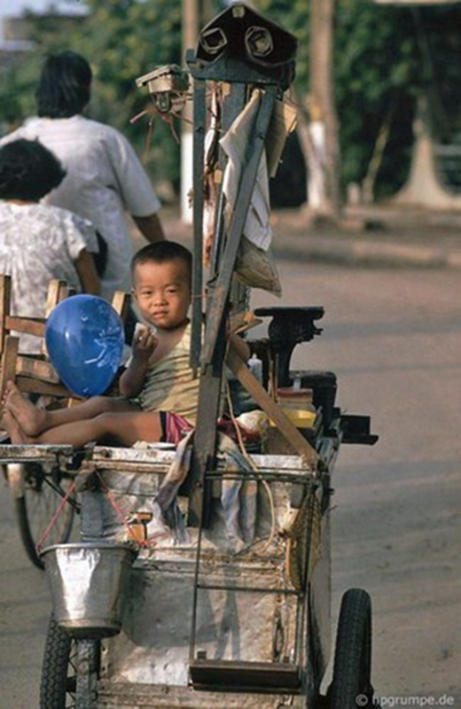 Một cậu bé ngồi trên chiếc xe đẩy bán khô mực nướng
