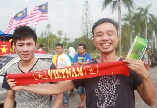 Văn Anh (phải) hạnh phúc khi mua được vé xem trận bán kết lượt đi AFF Cup 2014 giữa Malaysia và Việt Nam. Ảnh: Lâm Thỏa