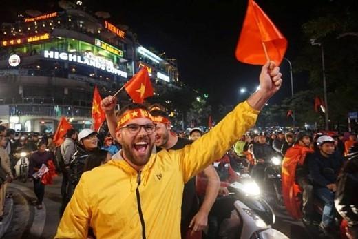 Các du khách nước ngoài mua cả cờ Việt Nam để ăn mừng.