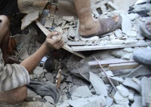 Cậu bé người Palestine, Mahmoud al-Ghol đang được các nhân viên cứu trợ đưa ra khỏi đống đổ nát sau khi ngôi nhà của mình sụp đổ tại thành phố Rafah, phía nam dải Gaza. Các cuộc tấn công và nã pháo giữa Isreal và Palestine vào tháng 7 và 8 đã khiến hơn 2.000 người thiệt mạng trong đó có nhiều trẻ em (Ảnh: Reuters)