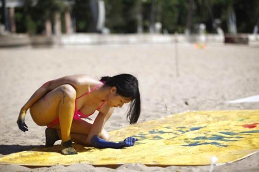 Hương Giang bất chấp nắng gắt đến bỏng da để vẽ tranh bằng thân thể.