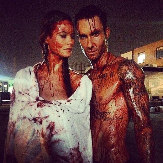 Behati Prinsloo và Adam Levine tạo dáng trước camera trong khi cơ thể dính đầy máu giả.