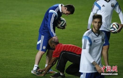 Một CĐV thoát khỏi sự ngăn cản của nhân viên an ninh khi vào sân để thể hiện sự hâm mộ với Messi. Anh lau giày cho Leo trong khi ĐT Argentina khởi động trước trận đấu bảng F gặp Iran tại World Cup 2014 vào ngày 21/6 ở Belo Horizonte (Brazil).