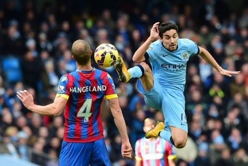Tiền vệ Jesus Navas tranh bóng quyết liệt với Brede Hangeland trong chiến thắng 3-0 của Man City trước Crystal Palace.