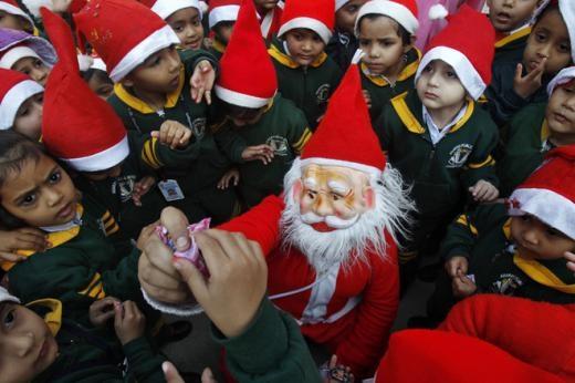 Một học sinh trong bộ đồ ông già Noel phân phát kẹo cho trẻ em ở thành phố Chandigarh, Ấn Độ. Ảnh: Reuters