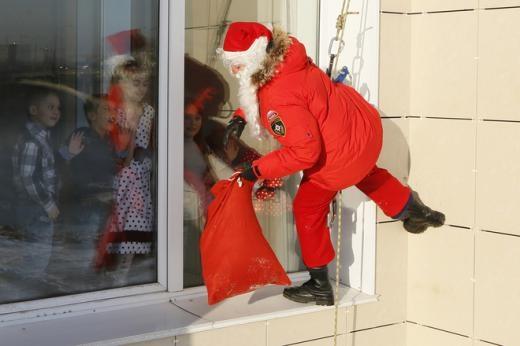 Alexei Trifonov, một thành viên của tổ chức dịch vụ Người giải cứu, mặc đồ ông già Noel, chuẩn bị phát quà cho nhân viên của Bộ Khẩn cấp Nga và con em của họ. Ảnh: Reuters