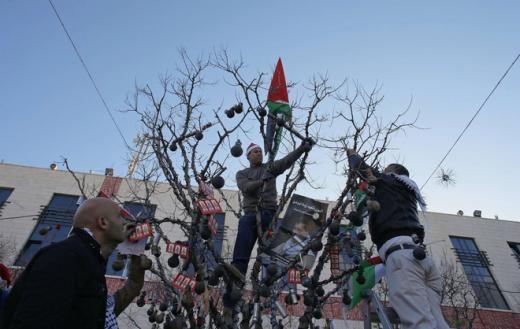 Người dân Palestine trang trí cây tại Quảng trường Manger Square. Ảnh: Reuters