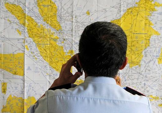Một quan chức tại sân bay kiểm tra bản đồ tại sân bay quốc tế của Indonesia