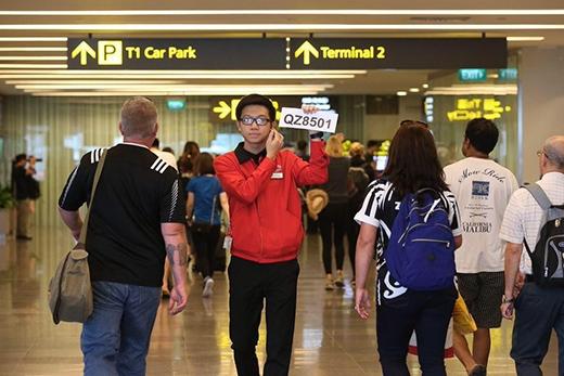 Nhân viên sân bay Changi cầm thông báo có số hiệu QZ 8501 để hỗ trợ thân nhân hành khách