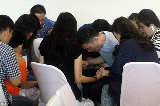 Thân nhân hành khách ngồi sát lại để cùng nhau cầu nguyện tin tốt lành sẽ đến