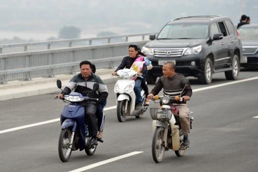 Nhiều người không đội mũ bảo hiểm, phóng lòng vòng quanh cầu ngắm cảnh.