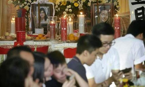 Gia đình đặt di ảnh của Thejakusuma và con gái trong buổi lễ hôm qua. Ảnh: Straits Times